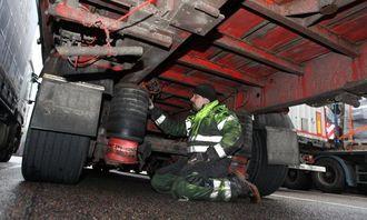 Mekaniker Sven Behr fra Bilgutta AS sjekker hva som kan være årsak til at ABS-en ikke virker på semihengeren bak den svenskregistrerte DAF-en.