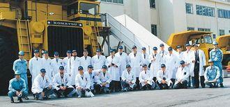 Hos Komatsu i Japan er det tradisjon at besøkende blir utstyrt med hvite frakker når de er på besøk. Delegasjonen ble fotografert i 1992. Skal vi gjette på at bildet ble tatt foran dumptrucken som senere gikk til Titania?