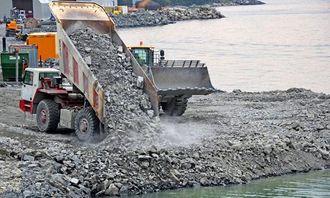 Store mengder steinmasse kjøres på sjøen.