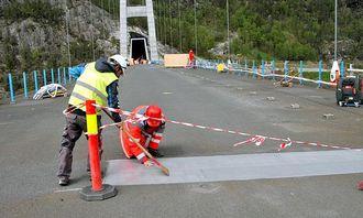 Siste finpuss på malingen. Sittende på huk kontrollingeniør Ketil Engen, Statens vegvesen.