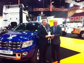 En fornøyd Ford-sjef Paul Randle (til venstre) sammen med juryforman Pieter Wieman og vinnerbilen.