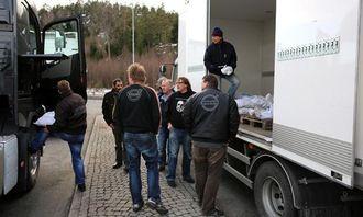 Per Danielsen fra Volvo Norge deler ut kjettinger til alle bilene ved tollstasjonen. Samlet vekt på kjettingene er over to tonn.