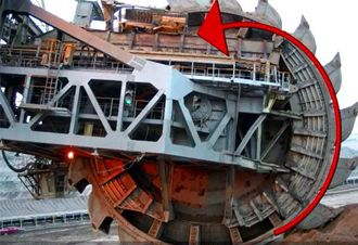 Cat D8R blir liten plassert oppe på transportbåndet til skovlehjul-graveren i brunkullgruven.