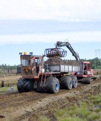 En spesialbygget Hymax 940 med 1 m brede belteplater og torvskuffe på 1,5 m3 laster torvdumperen.