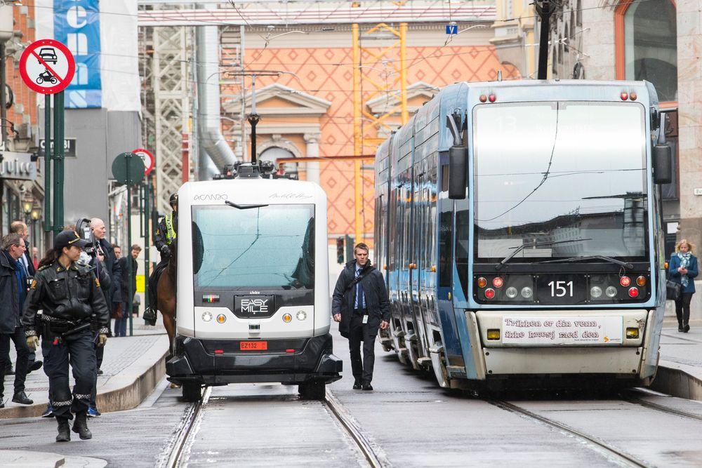 En selvkjørende buss på tur i Oslos gater i april i fjor, trygt flankert av politifolk og sikkerhetsvakter.