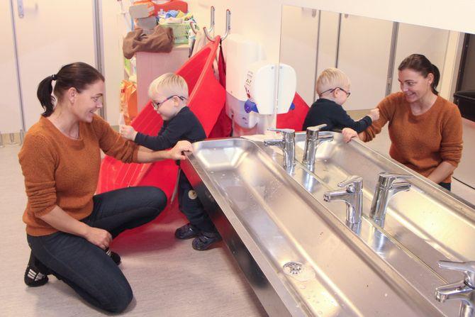 Pedagogisk leder i Læringsverkstedet Trålveien barnehage i Bodø, Marita Kolin, er Troys (3) egen ressursperson. – Vi er som et gammel ektepar, ler hun og får hjelp til å vaske seg på armene av treåringen.