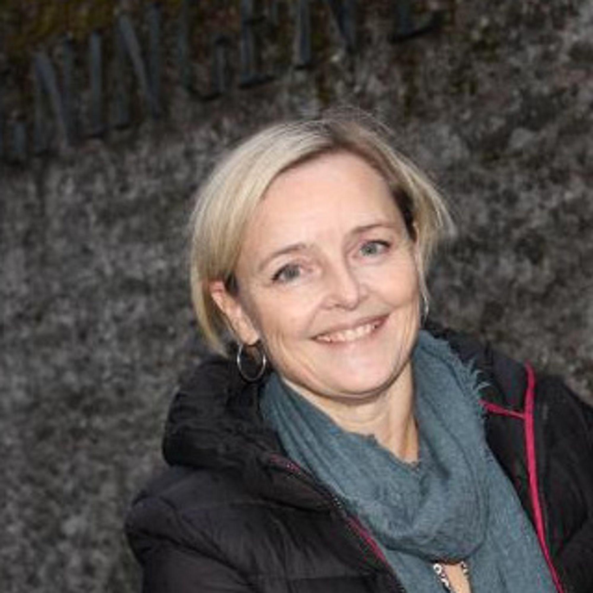 Foto av voksen vkinne med blondt hår skjøvet bak ørene, blått skjef og boblejakke. Hun ser rett i kameraet og smiler. I bakgrunnen er en grå steinvegg.