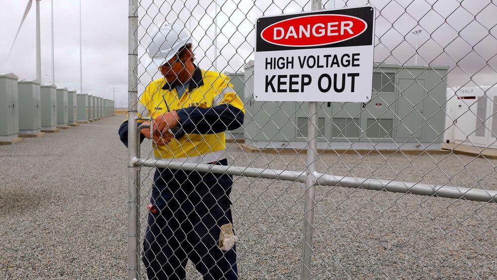 En arbeider sjekker hovedinngangen til verdens største litiumion-batteri under den formelle åpningen av anlegget nær Jamestown, Australia, 1. Desember i fjor. Ekstreme prissvingninger ga nylig penger i kassa hos den private aktøren Neoen.