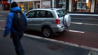 En sølv RAV 4 er parkert mot kjøreretningen i et klart oppmerket rødt sykkelfelt i Kongens Gate i Oslo sentrum. En person passerer på fortauet.