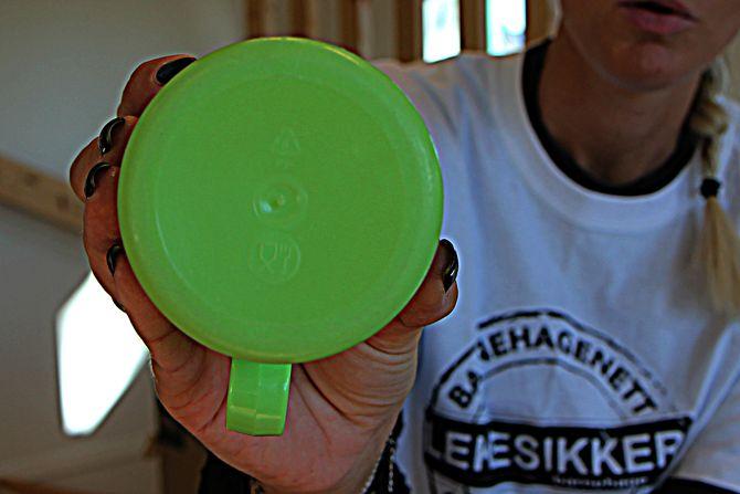 """Prosjektleder i """"Lekesikker barnehage"""", Turi Dolve Lund, holder opp en plastkopp som er merket med bestikk for å vise at det er egnet å spise med og på."""