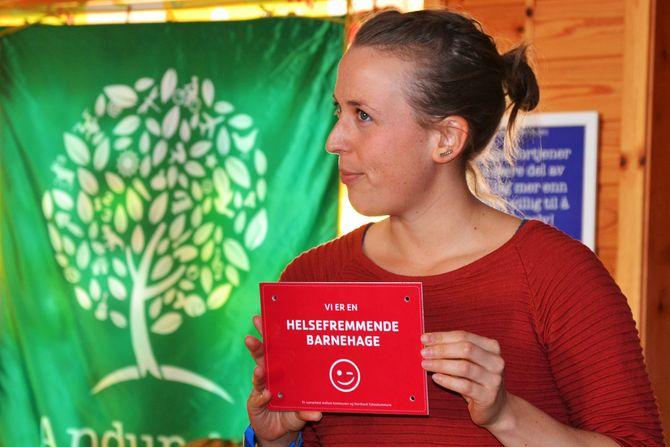 Folkehelsekoordinator i Andøy kommune, Katja Larsen, med skiltet som skal henges opp i barnehagen.