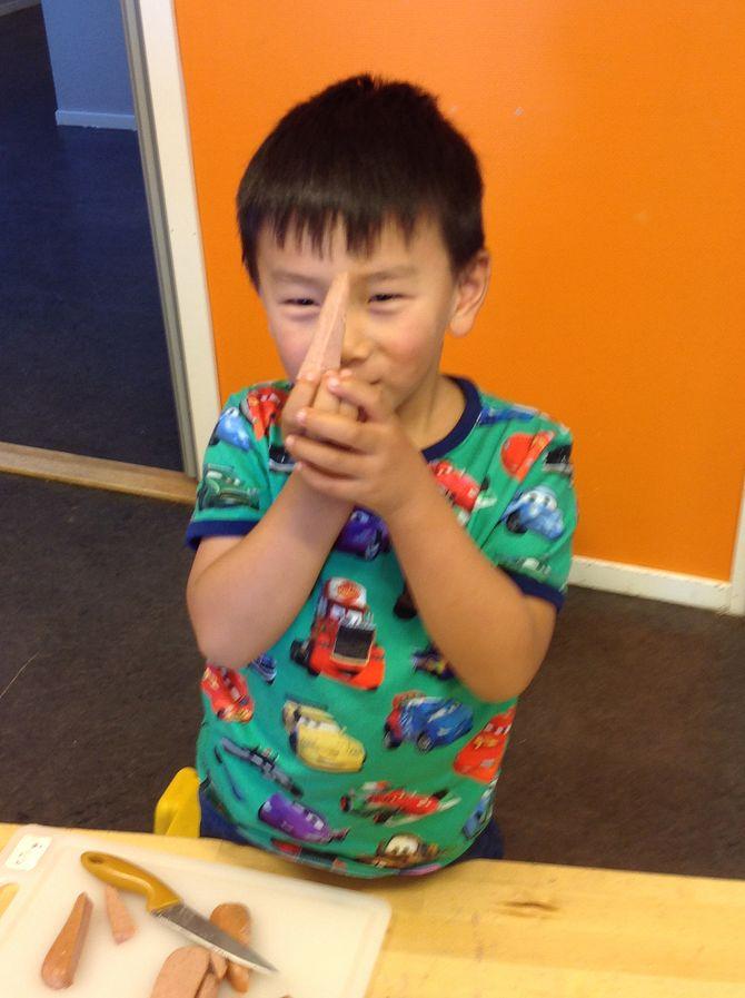 Alexander holder frem en av pølsebitene han har skåret opp til suppen.