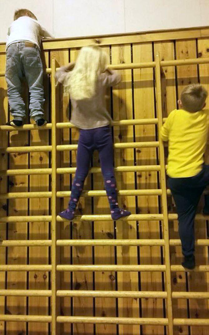 Barna ser ut til å ha det helt fint i idrettshallen mens de venter på at barnehagen skal bli klar til bruk igjen.