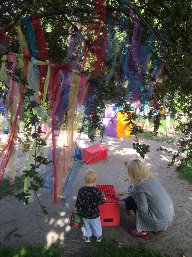 Barnehagen har fått mer farger på uteområdet. I lillehagen til de yngste er det blant annet hengt opp tøystrimler i sterke farger i trærne.