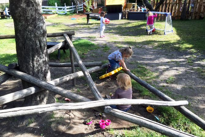 Personalet ønsker at barna skal kunne boltre seg i et naturlig miljø, derfor er trematerialer sentrale på barnehagens uteområde.