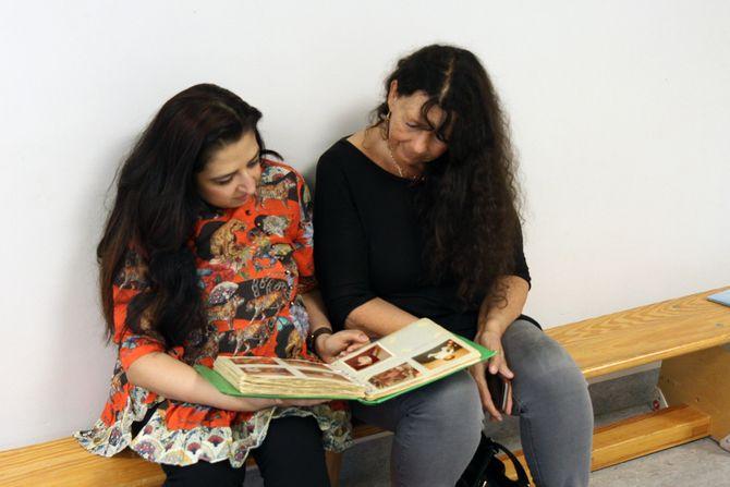Mahmona Khan og Rita Sharmila Lein ser på bilder fra den gang Lein jobbet i Åkeberg barnehage og Khan gikk i barnehagen.