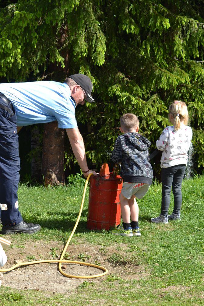 Også Østre Toten Brannvesen stilte opp. De hadde med en gammel vannpumpe som barna fikk prøve.