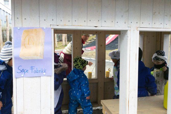 Da barnehagen skulle innvie sin nye lekeplass ble det arrangert «gammeldag». Hvert av de små trehusene på uteområdet ble gjort om til forskjellige arbeidsplasser som fantes på Lademoen før. Her får barna «lage» såpe på såpefabrikken.