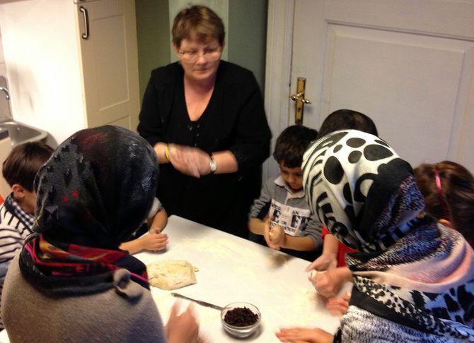 Barna fra Refstad transittmottak baker boller sammen med daglig leder Birgit Somby.