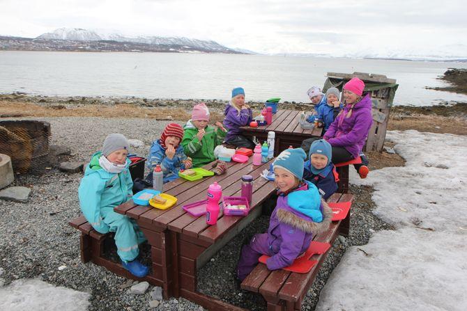 Ungene i Tusseladden friluftsbarnehage er enige om at maten smaker best ute. Her nyter de formiddagsmaten sammen med Lisa Strøm Brovold.