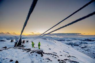 Tre kraftlinjer går inn i bildet der to personer arbeider på en fjelltopp. Det er dekket av snø og solen går ned i bakgrunnen.