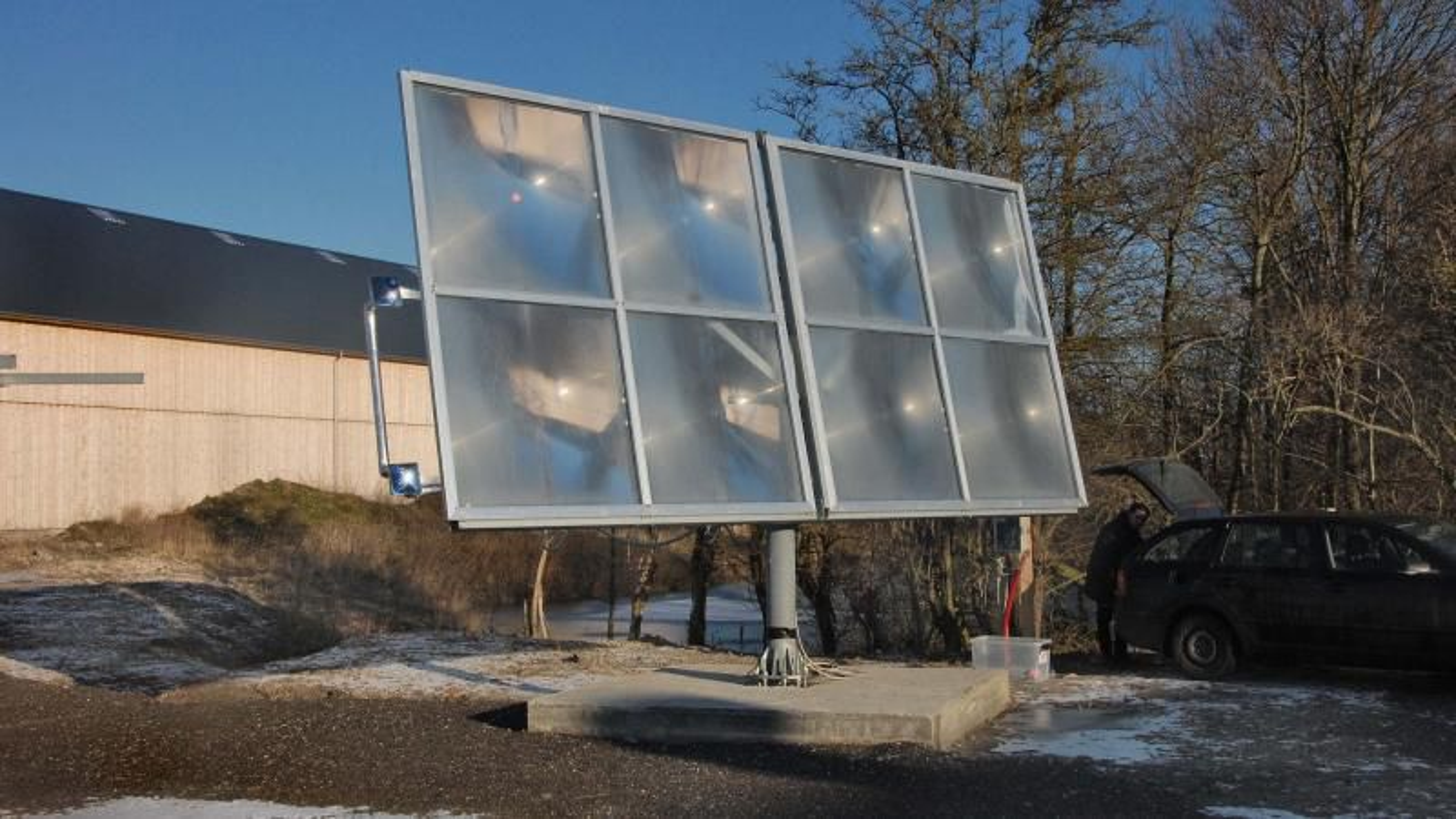 Ved en gård rett ved Sorø har Heliac testet prototypen på solvarmeanlegget sitt. De store kvadratene konsentrerer sollyset i et punkt to meter bak linsene. Her overføres varmen til en sirkulerende væske. Hele panelet vender seg, slik at det følger Solens gang på himmelen.