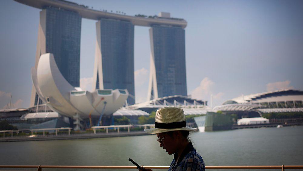 En turist sjekker smarttelefonen i Marina Bay Sands, Singapore. Byen er på topp i smartbyundersøkelser. Men på noen områder ligger Norge foran.