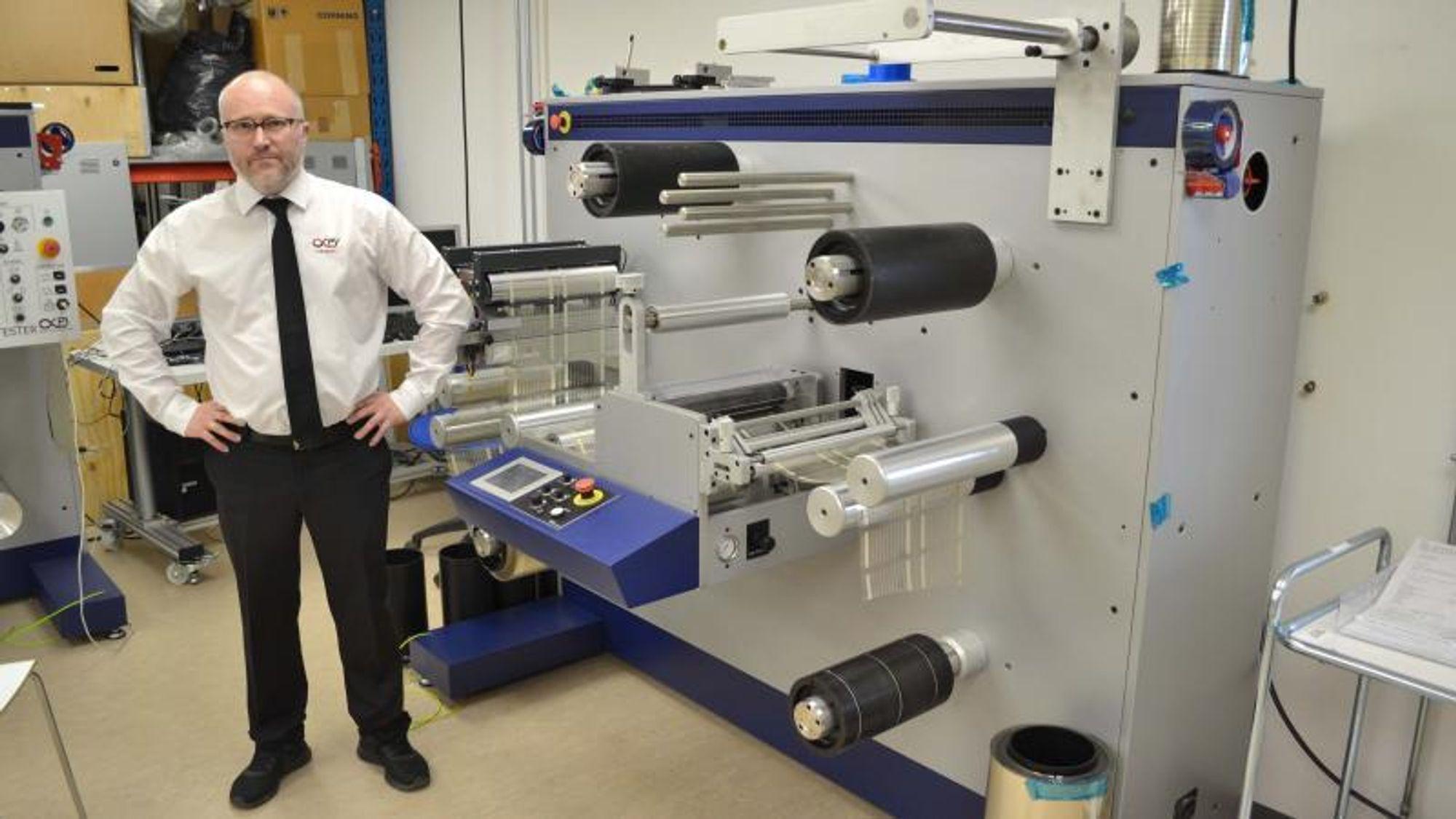 Infinity PV står selv for alle leddene i produksjonen av plastsolceller – fra produksjon av blekket til den tynne plastfolien over trykket, til forsegling av de ferdige solcellene. Til venstre står Frederik Krebs foran firmaets foliehåndteringsmaskin.