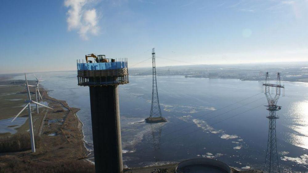 En skorstein midt inne mellom Amagerværkets blokker i København skal vekk. En fjernstyrt gravemaskin på toppen klarer oppgaven nøyaktig og kontrollert.