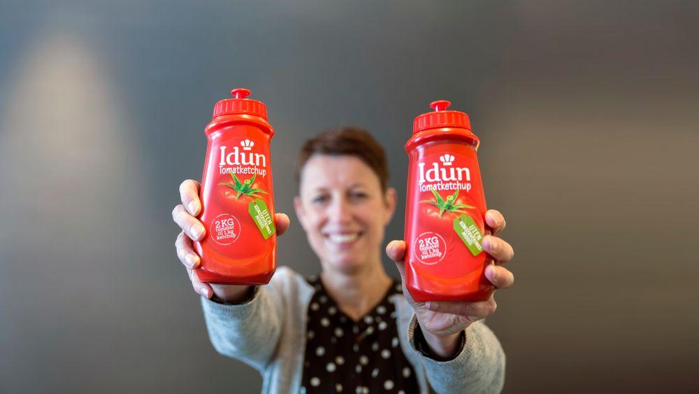 Plasttypen i etiketten er det som skiller de to ketchupflaskene Kjersti Hurum Trømborg, fagsjef emballasje i Orkla Foods Norge, holder opp her. Ved å bruke samme plasttype i etikett og flaske, økes gjenvinningsgraden betraktelig.