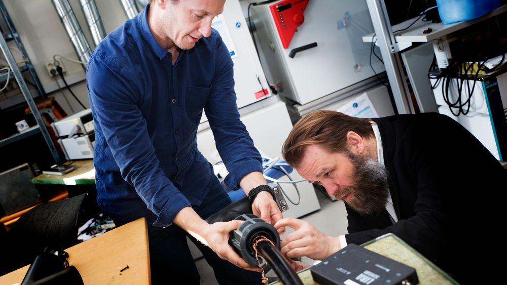 Sigbjørn Kolberg, forsker ved Avdelingen for smarte sensorsystemer ved Sintef Digital og Morten Huseby, daglig leder i Wirescan, monterer det nyutviklede målesystemet på kabelen i kjelleren hos Sintef.