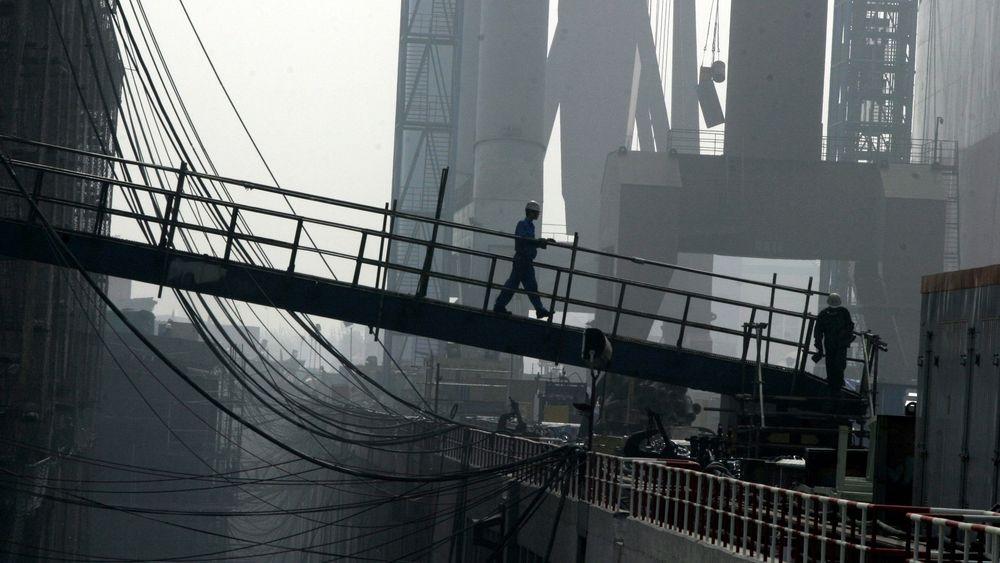 En kinesisk verftsarbeider går over broen som leder til et fraktskip for råolje på Dalian New Shipbuilding Heavy Industry Co. Ltd i Dalian i nordøstlige Kina.