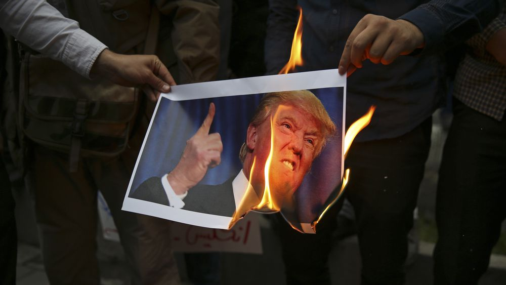 Demonstranter brenner et bilde av USAs president Donald Trump under en demonstrasjon foran USAs tidligere ambassade i Teheran, Iran, onsdag 9. mai i år, som en respons på Trumps beslutning om å trekke USA ut av den internasjonale atomavtalen og fornye sanksjoner mot landet.