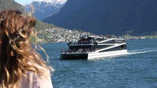 Future of the Fjords, som er 100 prosent elektrisk, møter hybridfartøyet Vision of the Fjords like ved Flåm i Aurlandsfjorden. Begge turistbåtene er bygget av Brædrene Aa i karbonfiber for The Fjords.