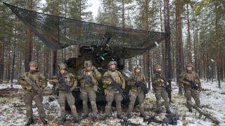 Bildet viser norske soldater i kamuflasjeuniform og med våpen på øvningsfeltet ved Rena militærleir.