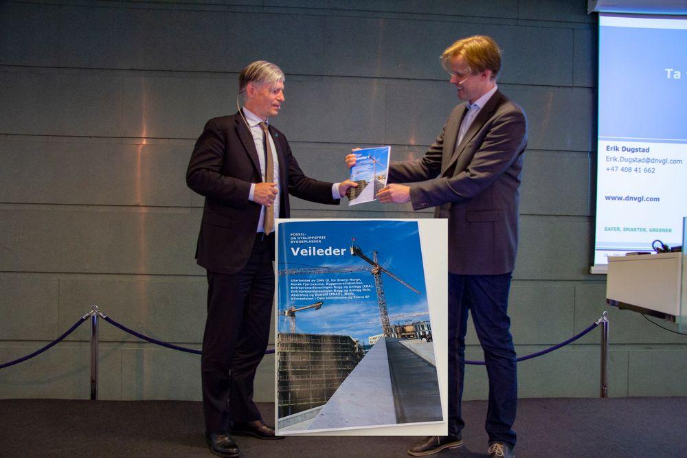 Trygve Mellvang-Berg, kommunikasjonssjef i Norsk Fjernvarme overrekker den nye veilederen for fossil- og utslippsfrie byggeplasser til klimaminister Ola Elvestuen.