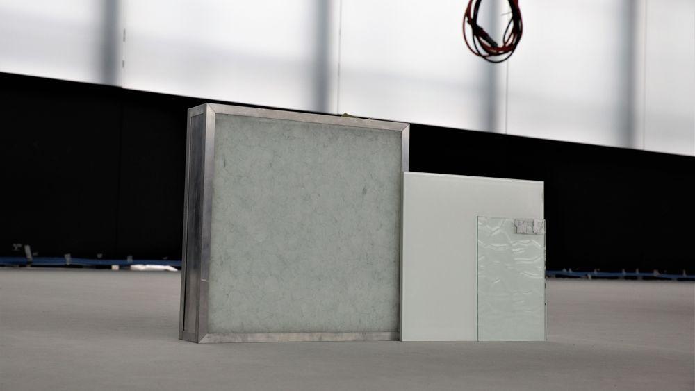 Det keramiske glasset (til venstre) og det folierte glasset Statsbygg skal teste. I det høyre hjørnet  ses en bit av en ruglete overflate som også vil bli testet, mens en prøve med frostet overflate ennå ikke er ankommet byggeplassen.