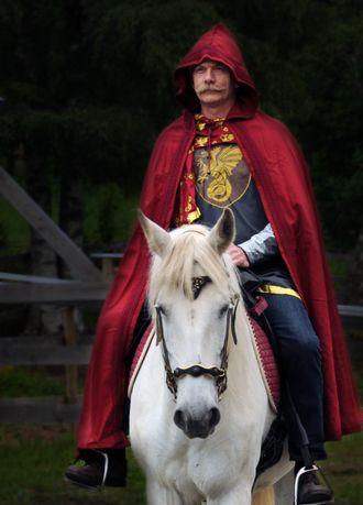 Kong Oustad kommer ridende.