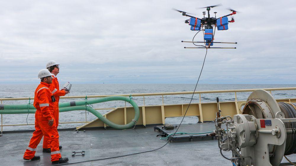 FISKEDRONE: Fartøysjef og gründer Pouyan Hamidiasl og pilot Henning Pedersen på tokt i Nordsjøen. Dronen har et ekkolodd hengende i en kabel under seg.