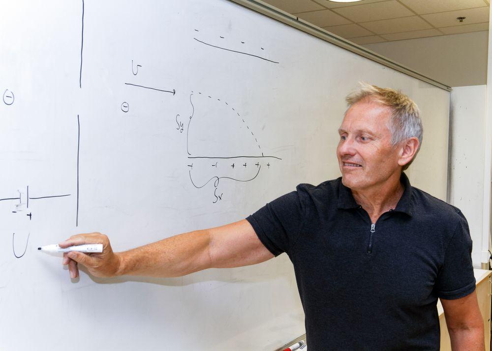 Einar Rasmussen bruker mye tavle og mindre lærebøker i sin undervisning. Her forklarer han hvordan man regner ut forholdet mellom høyden et elektron er skutt ut fra og hvor langt det går. Denne oppgaven kom i årets eksamen for elevene.