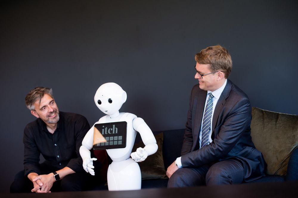 Robotvenner: Advokat og partner i Brækhus, Christian Bendiksen(t.h.) og CEO i Itch, Eirik Norman Hansen, har sammen skrevet en kronikk om eierskap og ansvar for kunstig intelligens – her med roboten Pepper.
