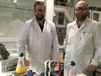 På bildet viser Jens Muff (tv) og Jens Laurids Sørensen batteriets teknologi i form av den lille prototypen.