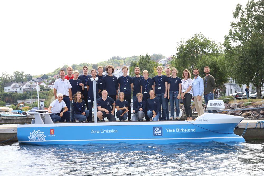 Studentprosjekt Kongsberg Maritime/FFI 2018: Smartship. De 16 studentene og veiledere og prosjektledere fra Kongsberg Maritime foran modellen de har utstyrt og testet.