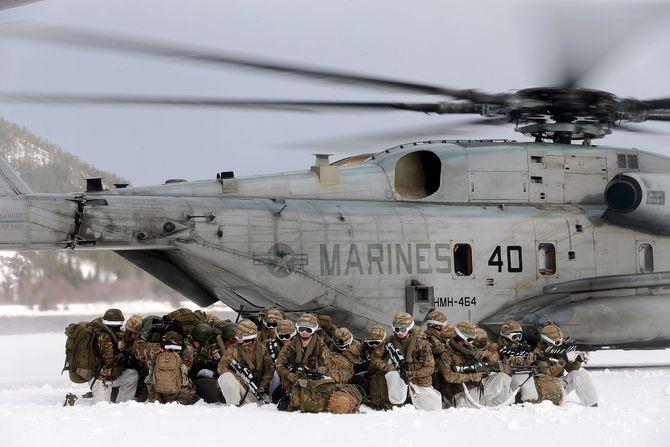Nederlandske marine infanterister sitter i kringvern på bakken da to Amerikanske CH-53E Super Stallion helikopter tar av under vinterøvelsen Cold Response 2016.