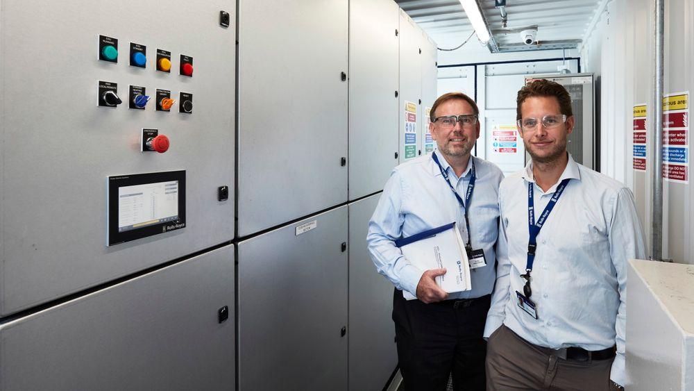 Teknisk produktsjef for energilagringssystemet Save Energy, Jens Hjorteset (t.h) og plassjef Erling Johannesen ved Rolls-Royce avdeling for Power Electric Systems i Bergen i det første komplette hybridsystemet, bygget i en container.