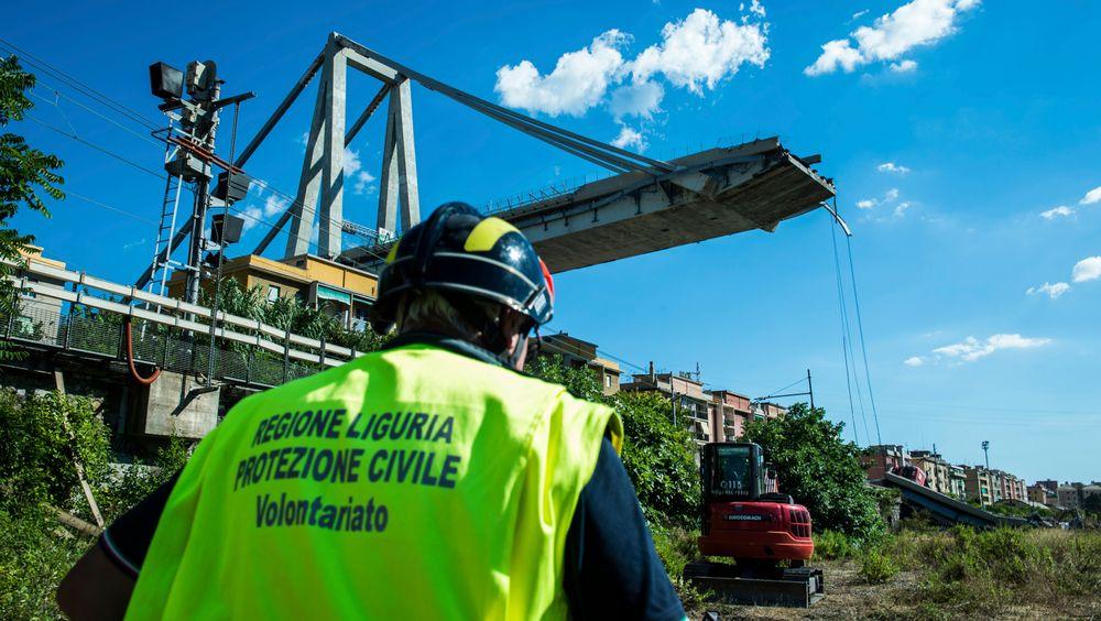 En arbeider inspiserer området rund Morandi-broen i Genova, som raste sammen tirsdag forrige uke.