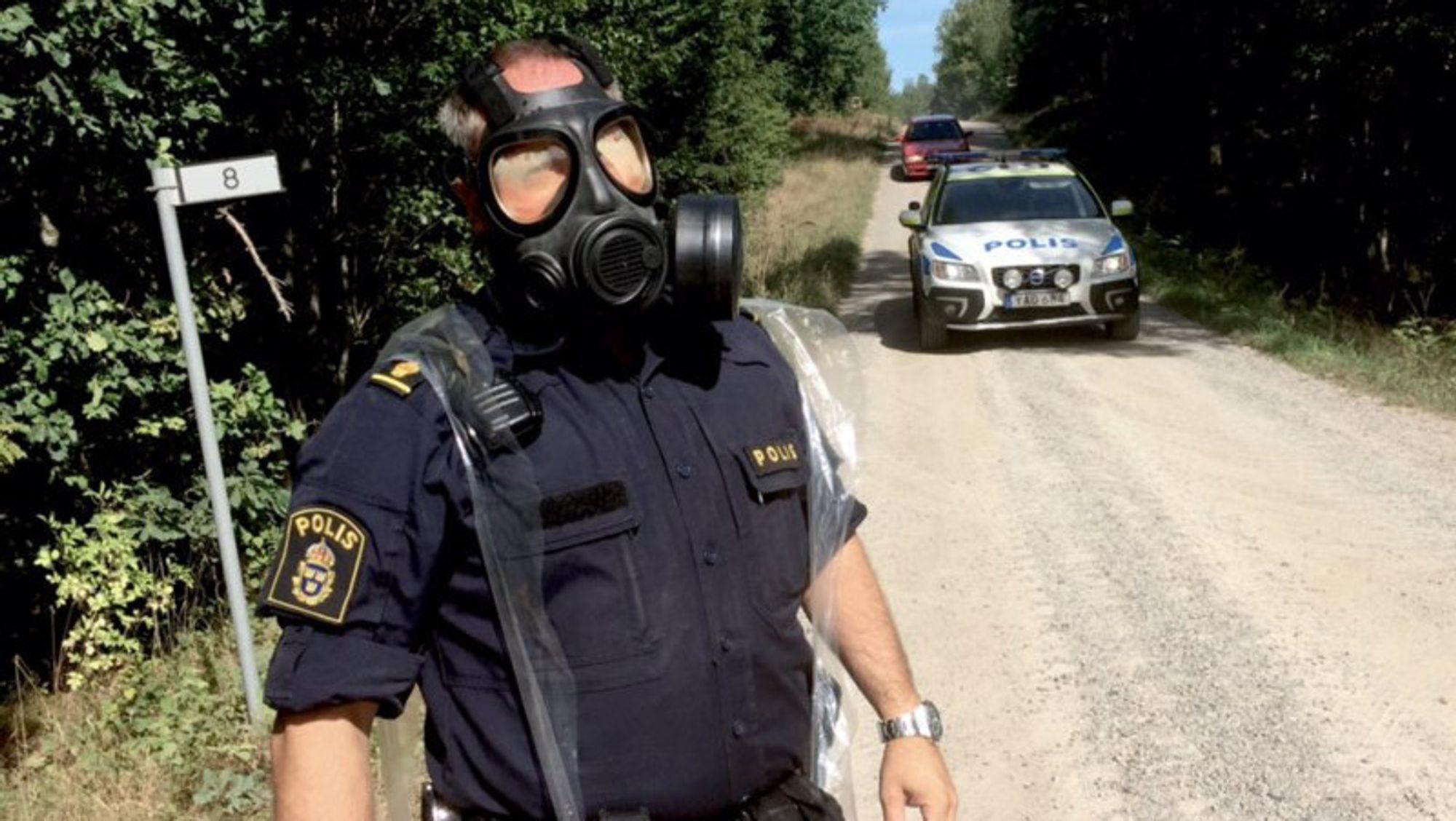 En politimann med gassmaske ved sperringene i nærheten av der flyet styrtet. Politiet ber folk holde seg unna for ikke å puste inn røyk.