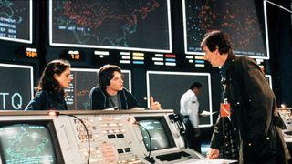 Scene fra WarGames-filmen med skuespillerne Ally Sheedy, Mathew Broderick og John Wood. I bakgrunnen sees noen av de store skjermene til WOPR-datamaskinen til NORAD.