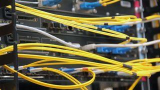 Nettverksrutere i et datasenter, med et stort antall gule fiberkabler.