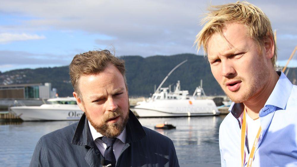 Eirik Hovstein i Maritime Robotics forteller ministeren at klyngesamarbeidet i Trondheim er viktig, men at det også er tøff konkurranse. En av Kongsberg Seatex' autonome livbåter, og Maritime Robotics' lille Oteren sees på vannet i bakgrunnen.